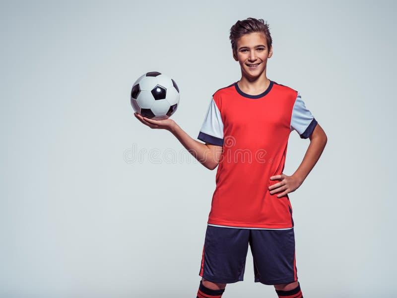 拿着足球的运动服的微笑的青少年的男孩 库存图片