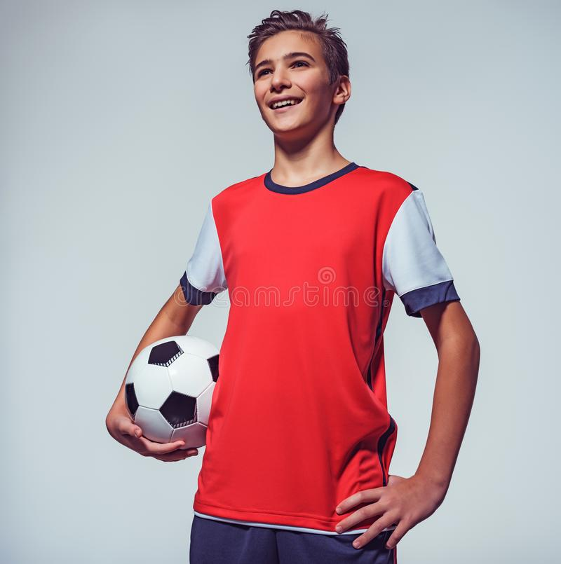 拿着足球的运动服的微笑的青少年的男孩 图库摄影