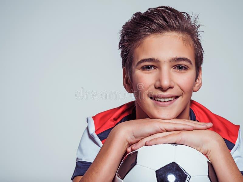 拿着足球的运动服的微笑的青少年的男孩 免版税库存照片