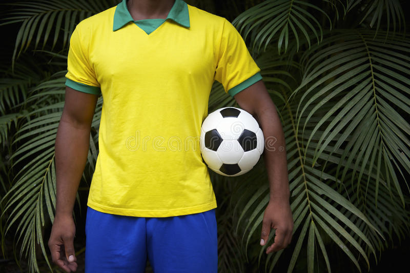 拿着足球的巴西足球运动员在密林 免版税库存照片