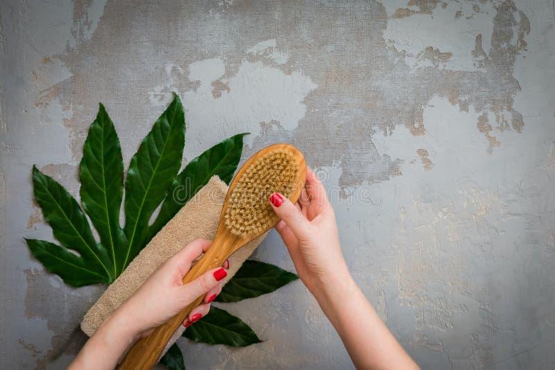 拿着身体温泉治疗竹刷子,绿色热带叶子背景的妇女手 免版税图库摄影