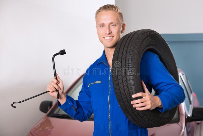 拿着轮胎和板钳的微笑的技工 库存照片