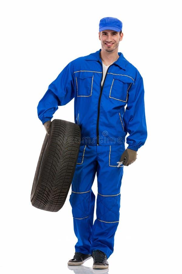 拿着轮胎的年轻技工 免版税库存图片