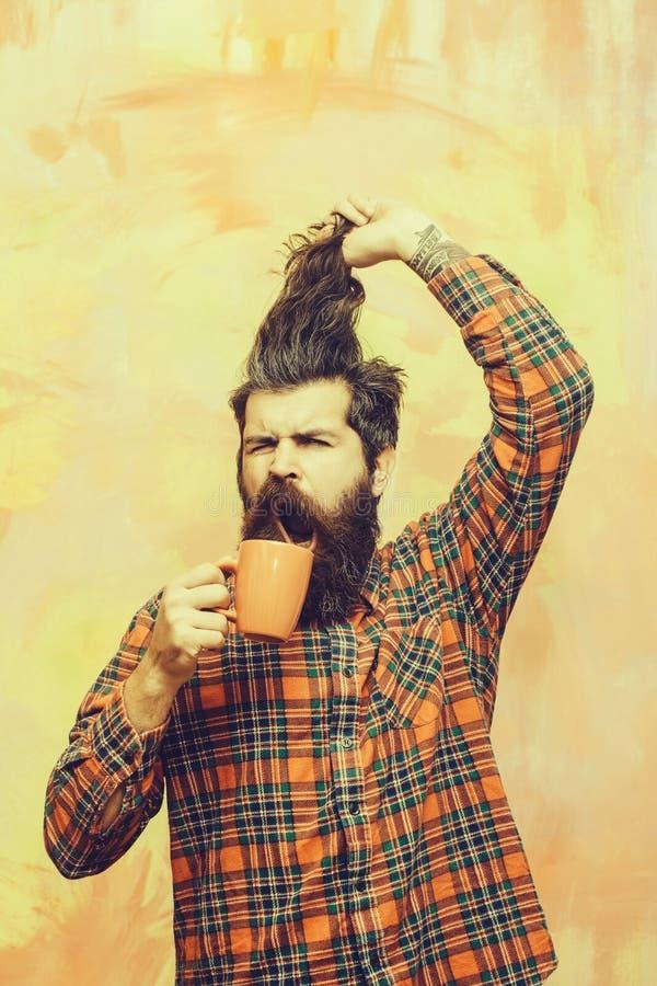 拿着边缘头发和橙色杯子的恼怒的有胡子的人 库存照片