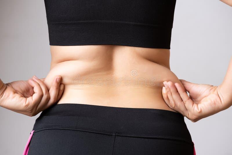 拿着过份腹部油脂的肥胖妇女手 医疗保健和妇女饮食减少腹部和塑造健康的生活方式概念 图库摄影