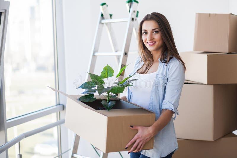 拿着运动的箱子的愉快的年轻妇女在空的屋子里在一个新房里 库存照片