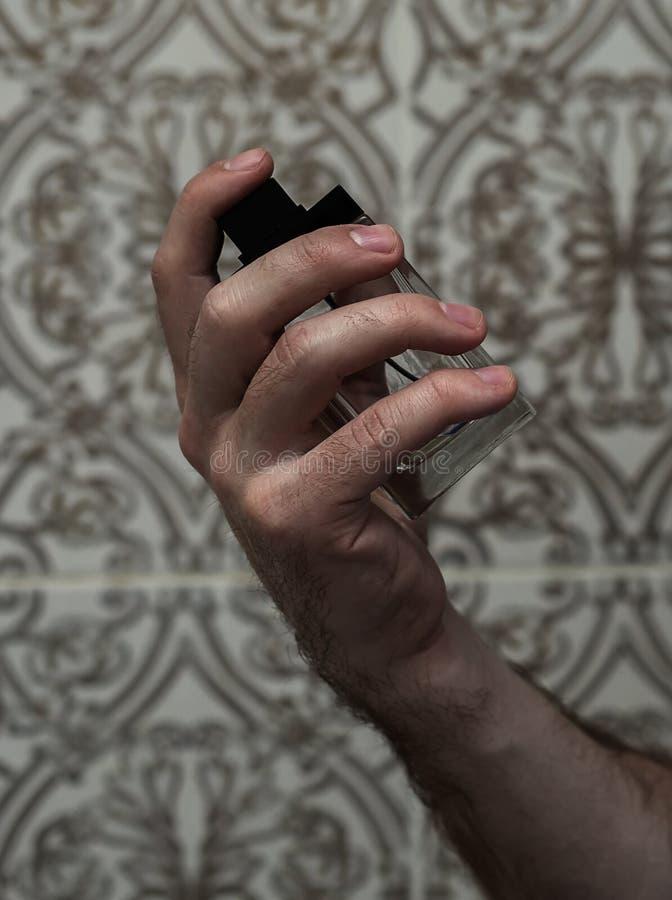 拿着透明香水的男性手 免版税库存图片