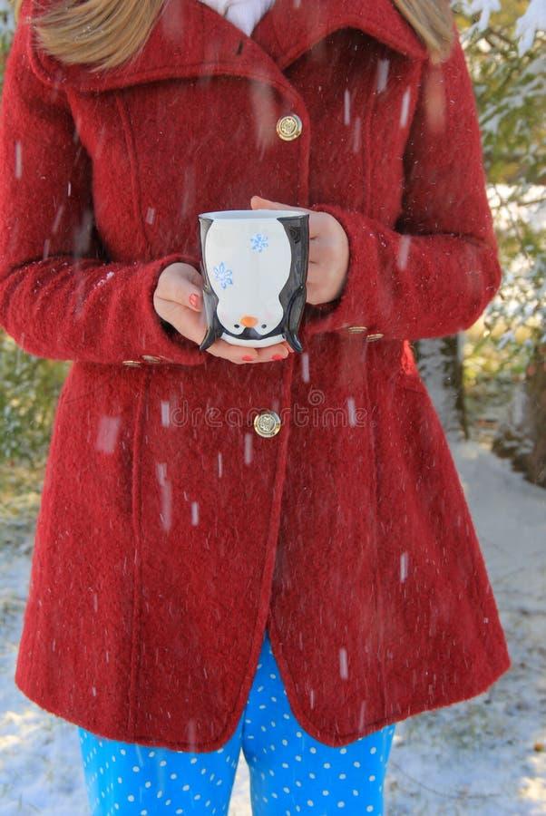 拿着逗人喜爱的企鹅咖啡杯外面在雪的红色外套的年轻金发的妇女 库存照片