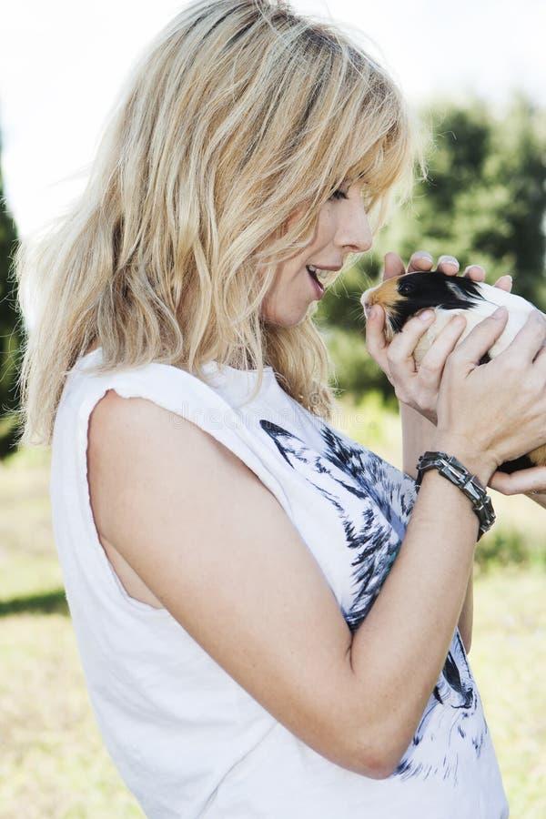 拿着逗人喜爱的宠物兔宝宝的美丽的金发妇女 库存照片