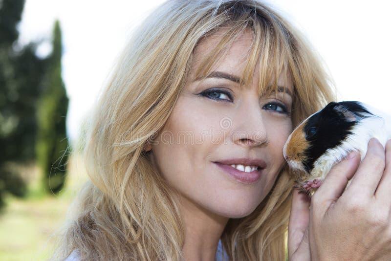 拿着逗人喜爱的宠物兔宝宝的画象美丽的金发妇女 库存图片