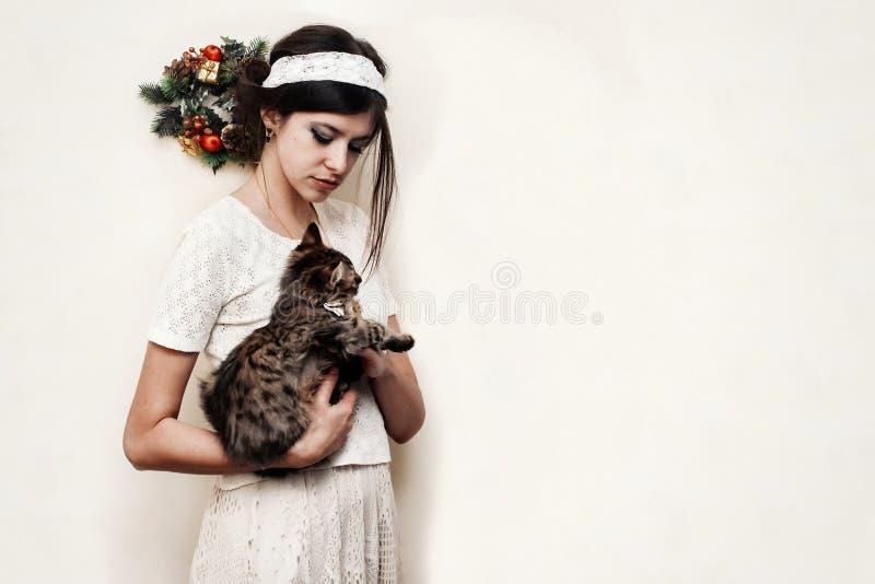 拿着逗人喜爱的滑稽的小猫与的葡萄酒礼服的美丽的妇女 库存照片