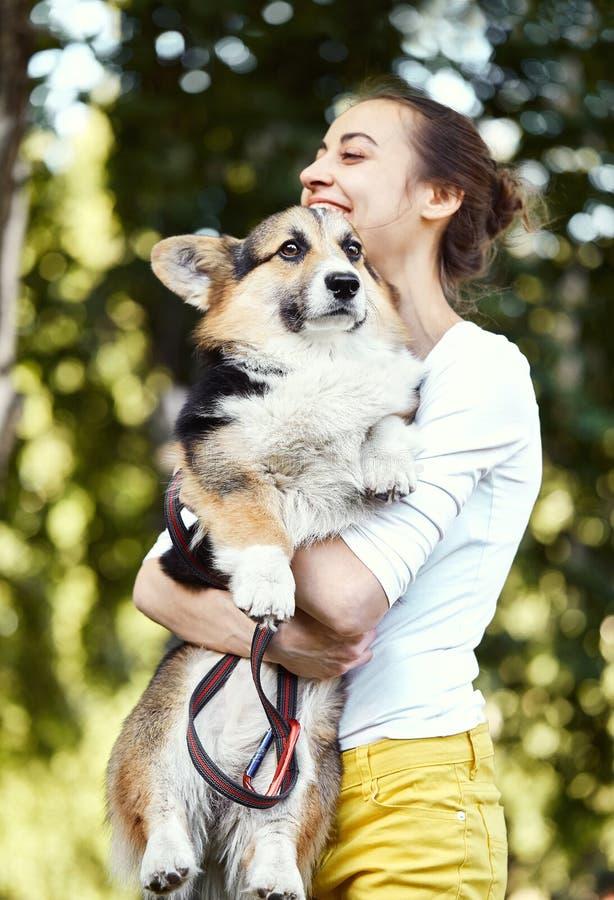 拿着逗人喜爱的狗威尔士小狗的微笑的年轻女人在公园户外 在狗的焦点 库存图片