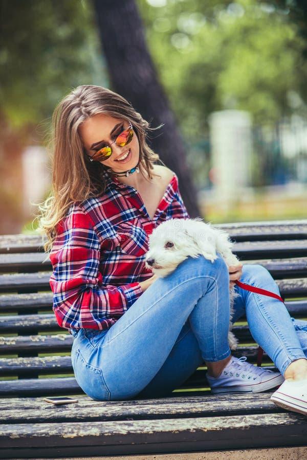拿着逗人喜爱的狗的可爱的愉快的微笑的少妇画象  免版税库存图片