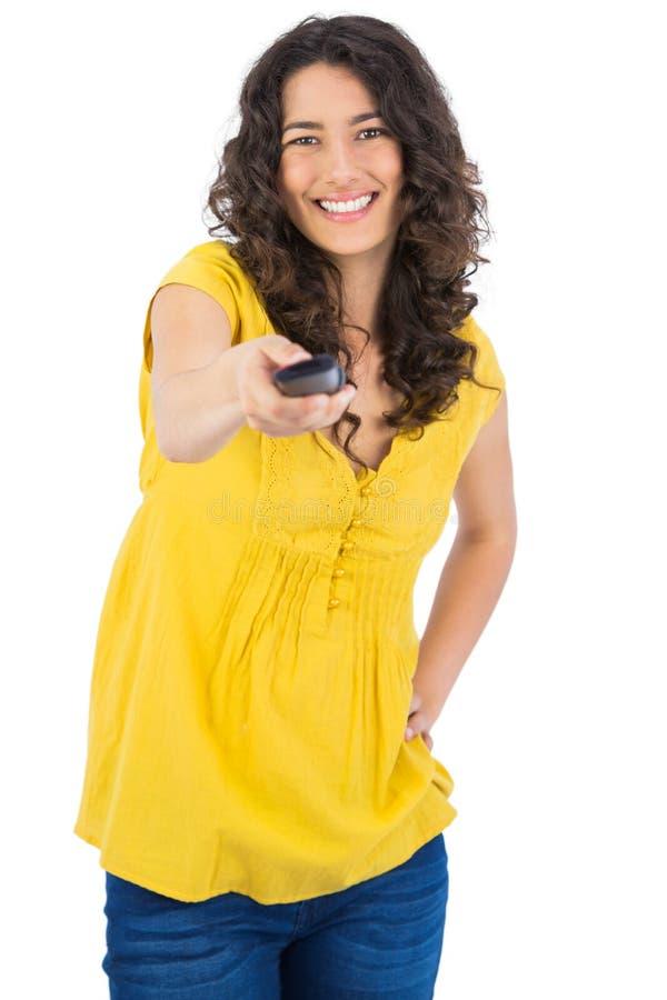 拿着遥控的快乐的卷发的俏丽的妇女 免版税库存图片