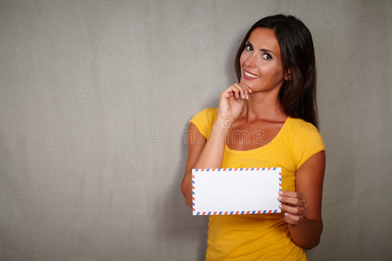 拿着邮件用在下巴的手的吸引人妇女 库存照片