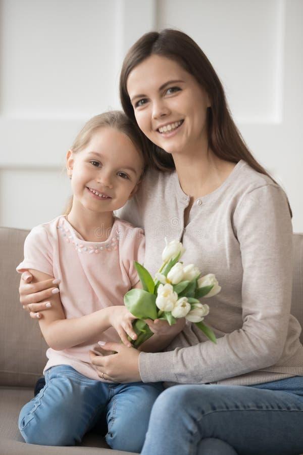 拿着郁金香的女儿在家与妈妈坐长沙发 库存照片