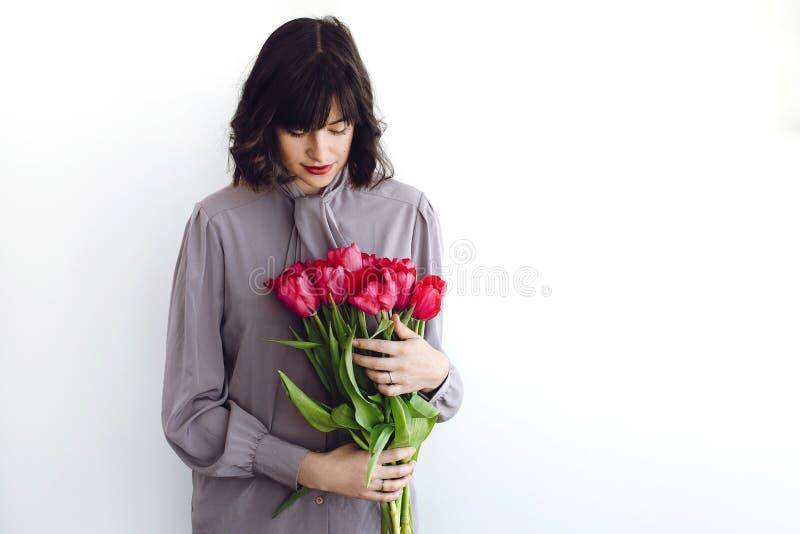拿着郁金香的时髦的花束在白色背景的美丽的深色的女孩户内,文本的空间 愉快的年轻女人与 免版税库存照片