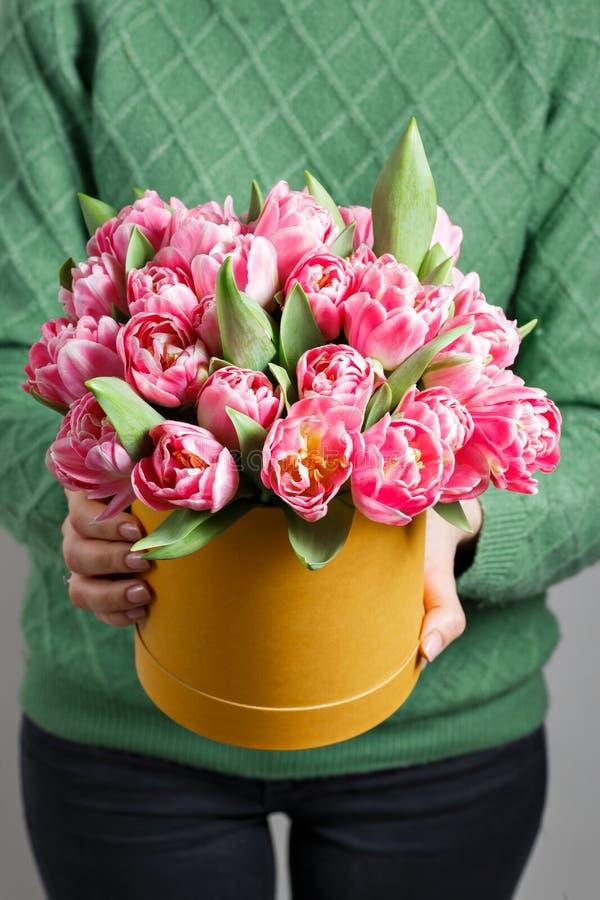 拿着郁金香的花束在礼物盒的年轻美丽的妇女 在一箱子或花束的桃红色颜色 3月8日的礼物 库存图片