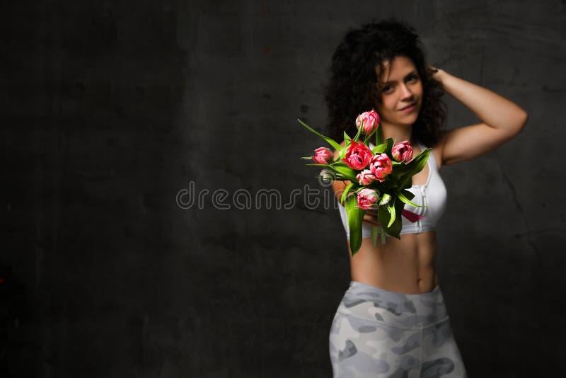 拿着郁金香的花束在颜色背景的美丽的妇女 库存图片