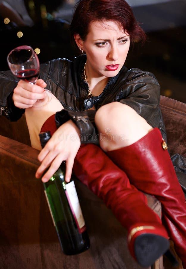 拿着酒杯和瓶的歪斜的俏丽的妇女 库存图片