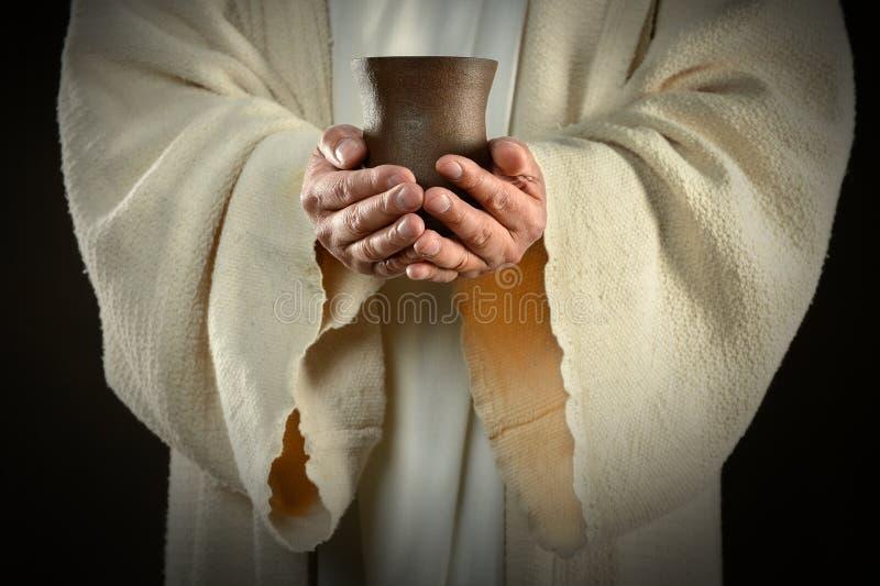 拿着酒杯的耶稣手 免版税库存照片