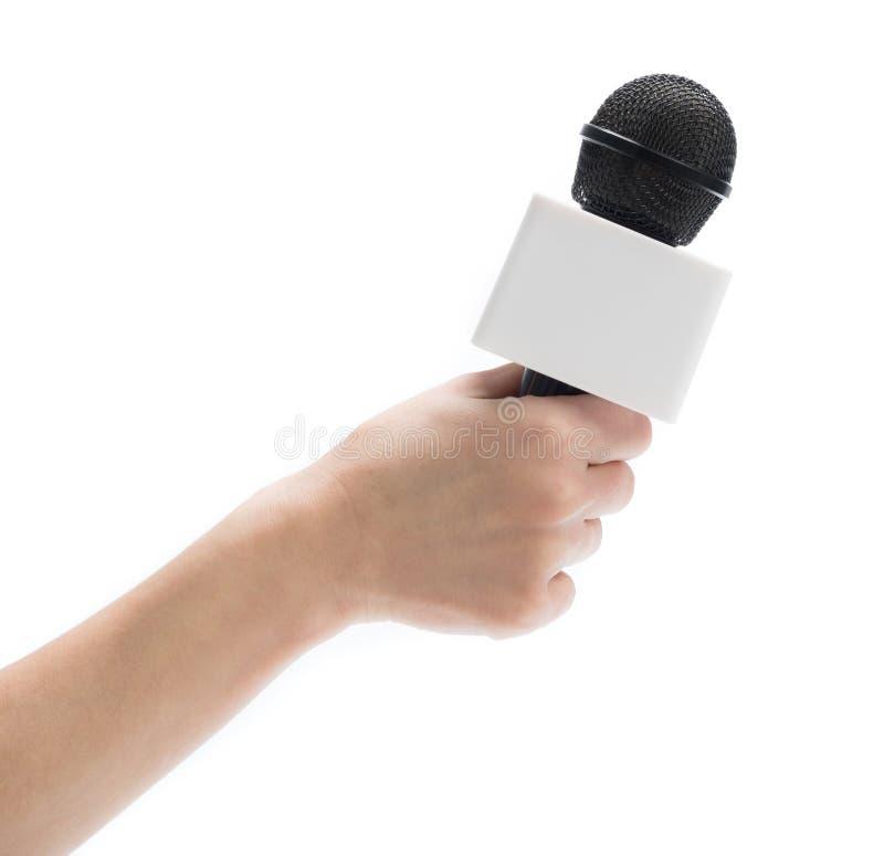 拿着采访的手话筒 免版税库存照片
