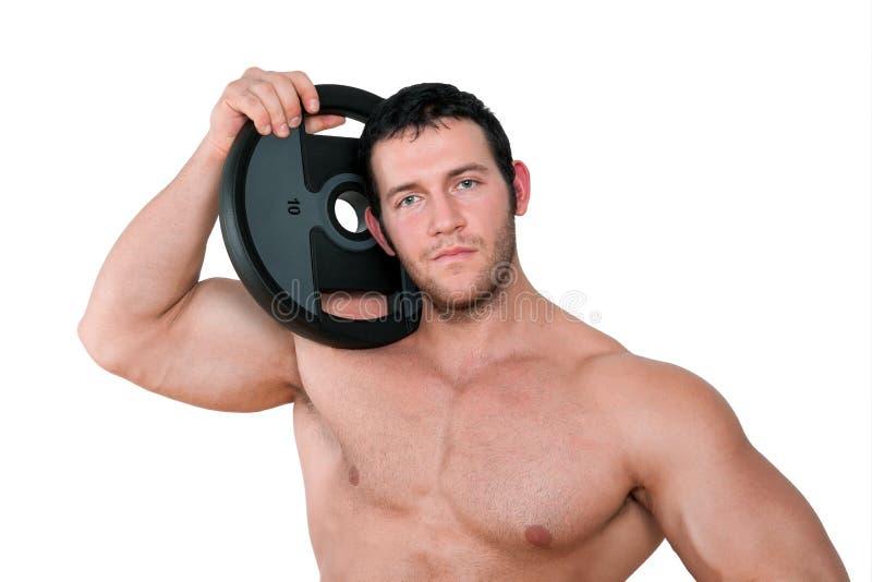 拿着重量的性感的爱好健美者。 免版税库存照片