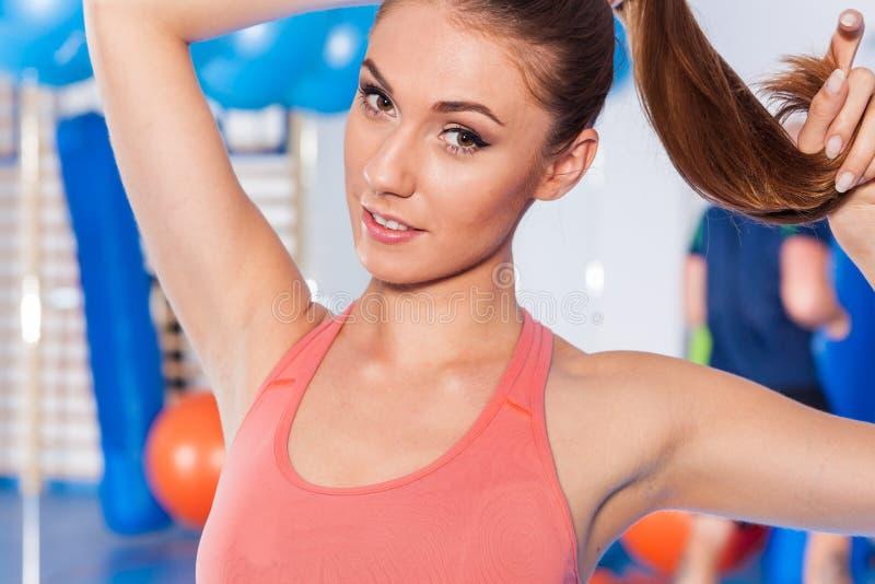 拿着重量(哑铃)和做健身indor的一名年轻俏丽的妇女的画象 Crossfit大厅 健身房射击 库存图片