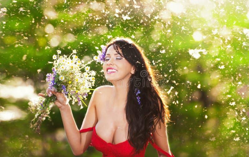 拿着野花花束的年轻妖娆的浅黑肤色的男人在一个晴天 美丽的妇女画象有低胸的红色礼服笑的 免版税库存图片