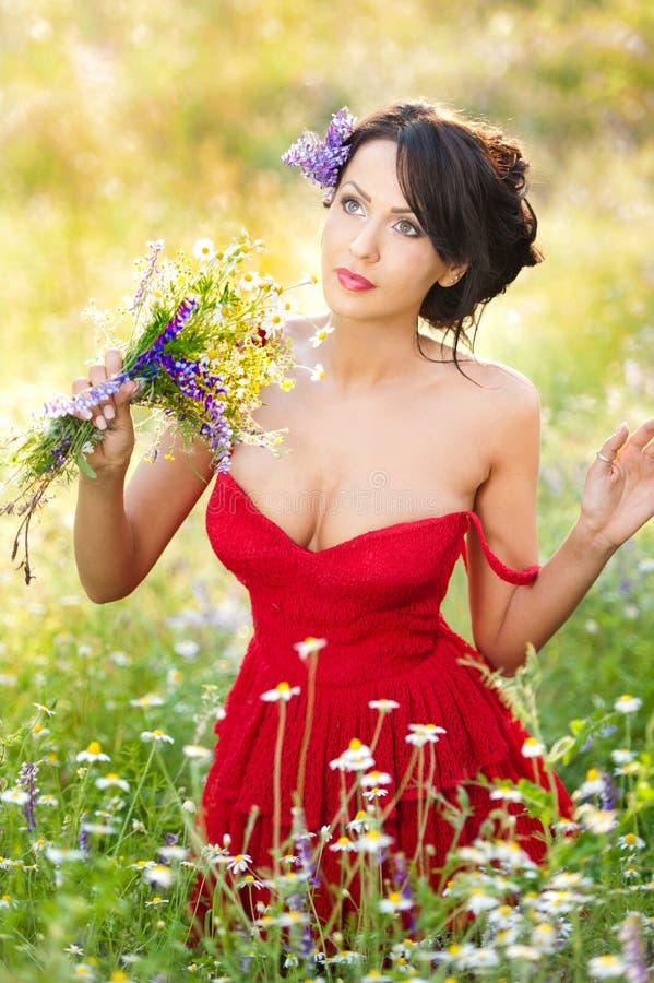 拿着野花花束的年轻妖娆的浅黑肤色的男人在一个晴天 美丽的妇女画象有低胸红色礼服摆在的 免版税库存图片