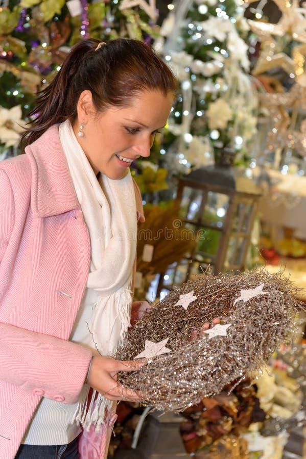 拿着金属圣诞节花圈的愉快的妇女 库存照片