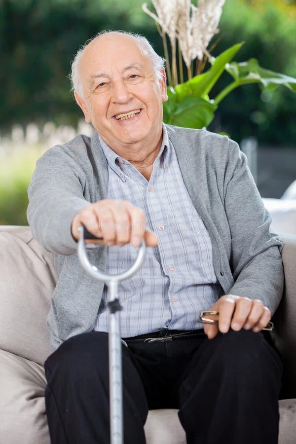 拿着金属藤茎的愉快的老人画象  免版税库存照片