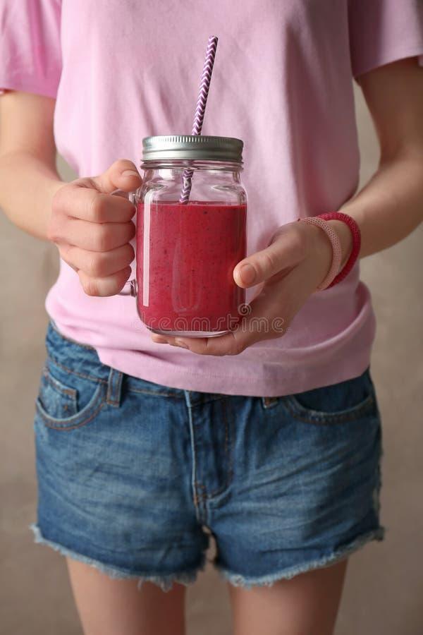 拿着金属螺盖玻璃瓶在灰色背景的新鲜的莓果酸奶圆滑的人的少妇 免版税库存图片