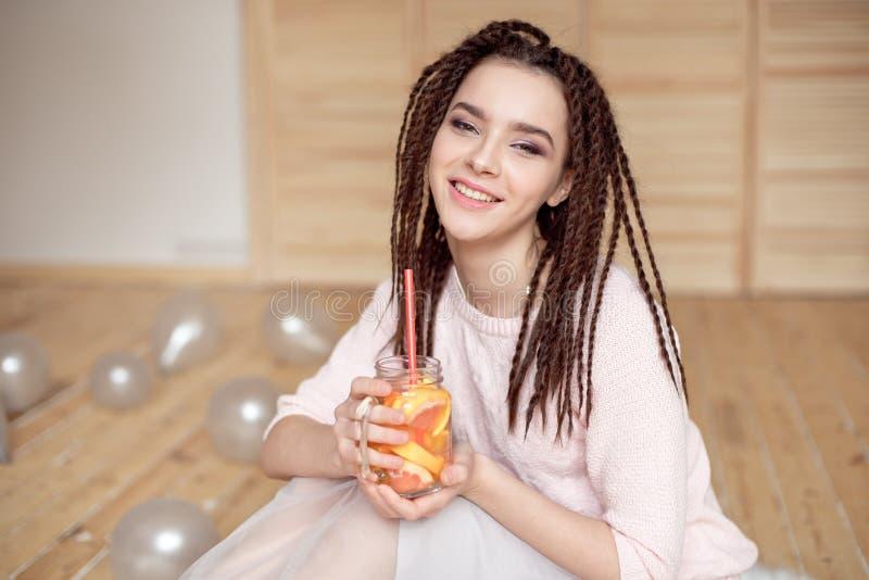 拿着金属螺盖玻璃瓶用柠檬水的年轻俏丽的妇女 图库摄影