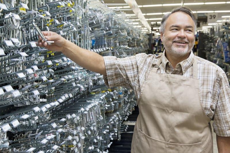 拿着金属设备的愉快的成熟推销员,当看在五金店时 免版税库存图片