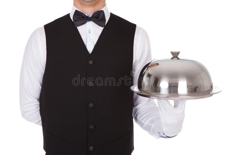 拿着金属钓钟形女帽在盘子的侍者盒盖盖子 库存照片