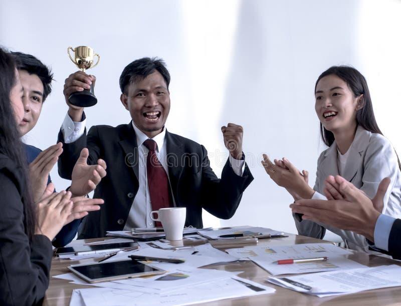 拿着金战利品的商人 的在办公室奖励的愉快和成功的企业队 免版税库存照片