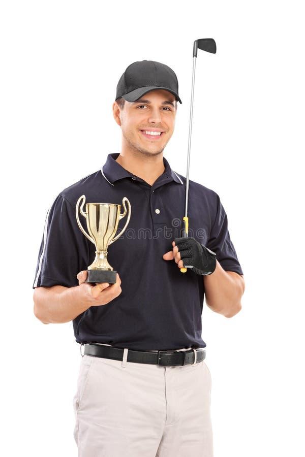 拿着金杯子的男性打高尔夫球的冠军 免版税库存照片