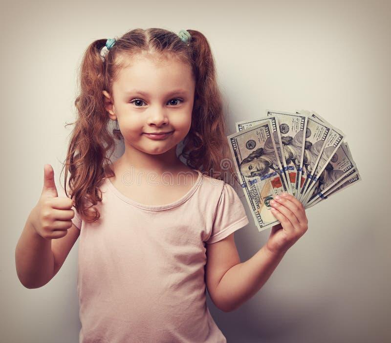 拿着金钱和显示赞许标志的愉快的富有的孩子女孩 vin 免版税库存图片