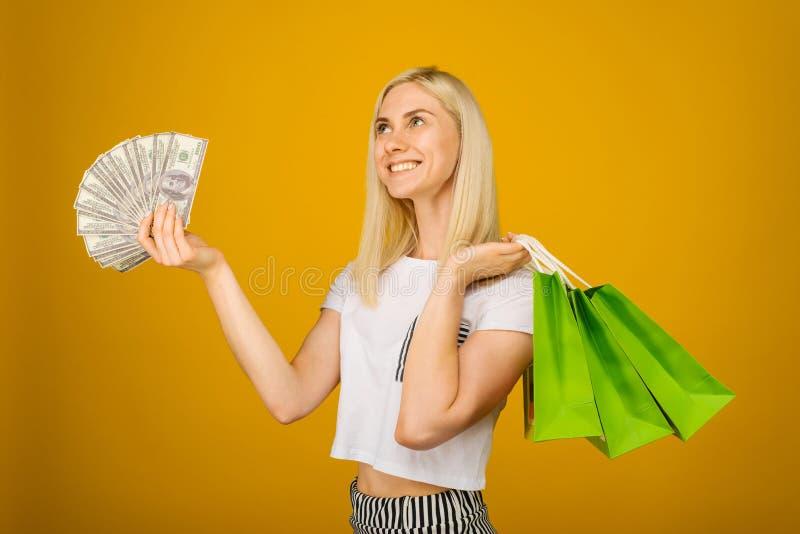 拿着金钱和绿色购物带来的愉快的年轻美丽的白肤金发的妇女特写镜头画象,隔绝在黄色背景 库存照片