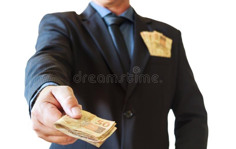 拿着金钱巴西人在他的手上和衣服口袋的商人 奶油被装载的饼干 库存图片