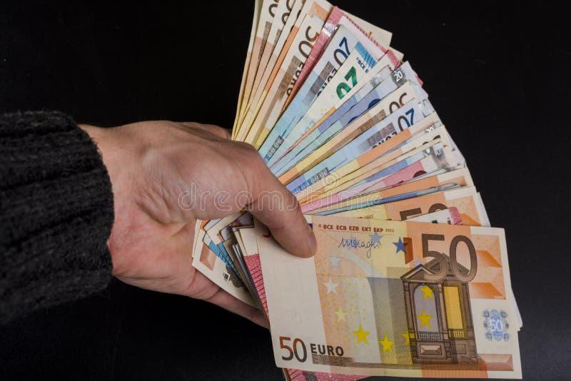 拿着金钱欧洲钞票的人的手被隔绝在深灰背景 图库摄影