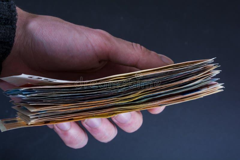 拿着金钱欧洲钞票的人的手被隔绝在深灰背景 免版税图库摄影