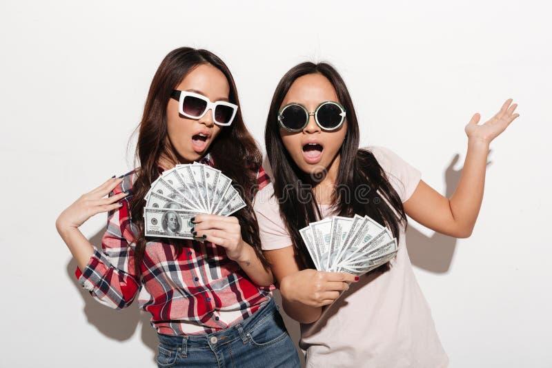 拿着金钱的两个亚裔凉快的夫人姐妹 库存照片