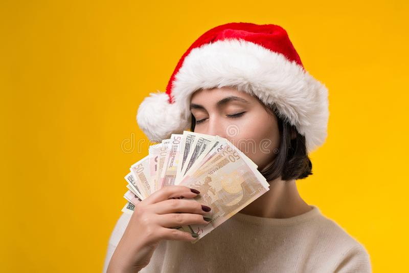 拿着金钱的圣诞节帽子的愉快的妇女 作梦关于圣诞礼物的逗人喜爱的女孩 妇女美元藏品爱好者在黄色的 库存图片