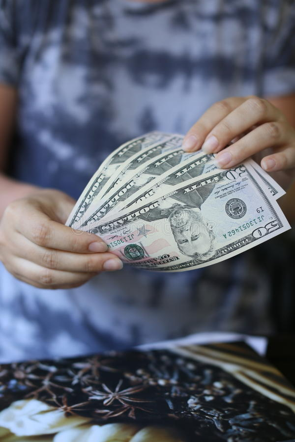 拿着金钱的妇女手 免版税库存照片