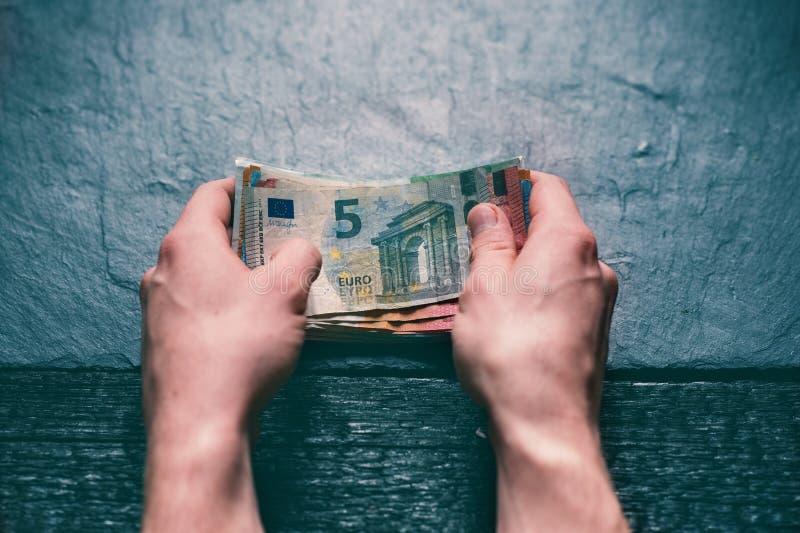 拿着金钱的年轻人HandÂ的 在石背景的钞票 另外价值欧元金钱钞票  免版税图库摄影
