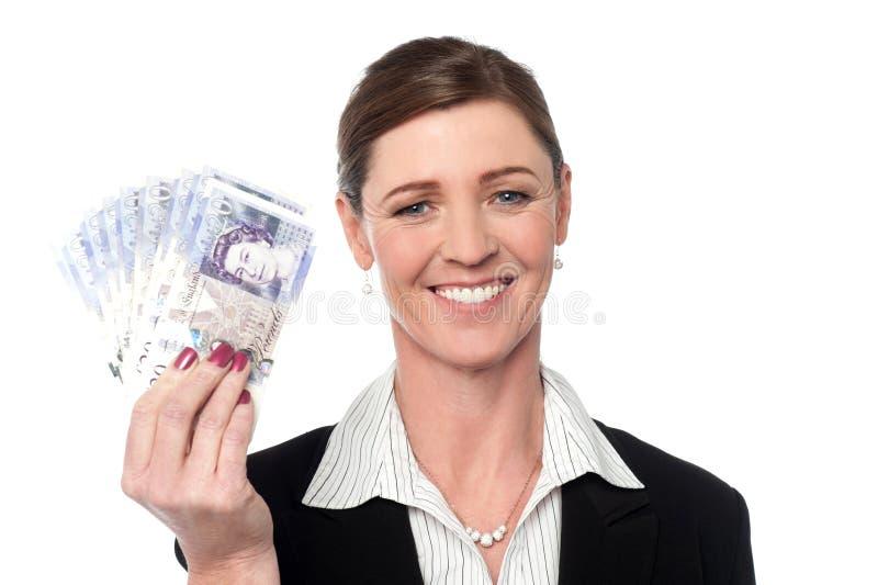 拿着金钱的微笑的女商人 免版税库存图片