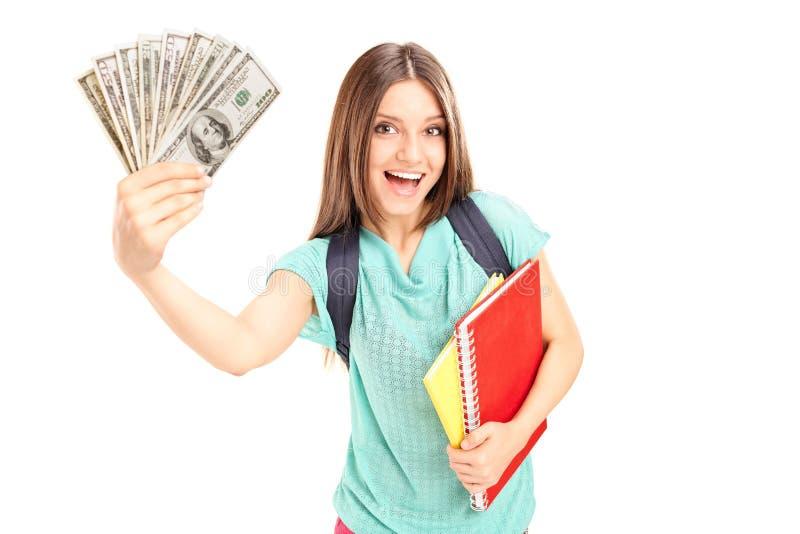 拿着金钱的快乐的女学生 免版税库存图片