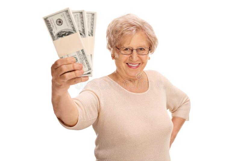 拿着金钱的快乐的成熟夫人 免版税库存图片